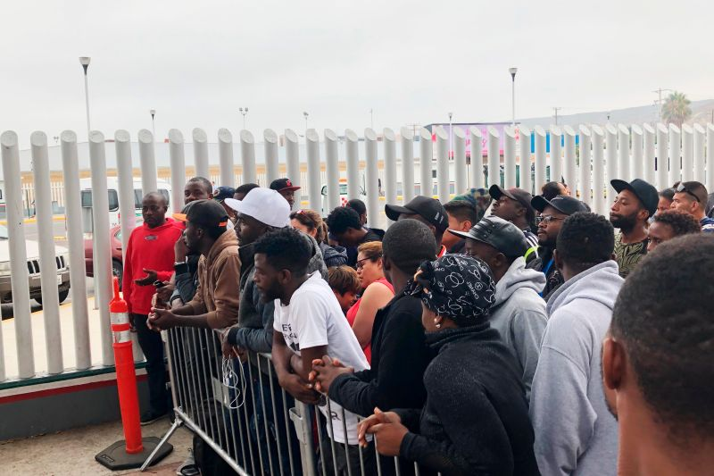 Migrants, many from Cameroon, listen to names being called in Tijuana, Mexico