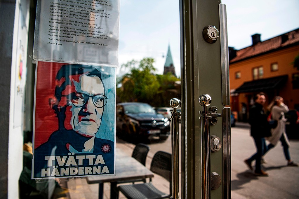 A sign instructing people to wash their hands—featuring a portrait of chief epidemiologist Anders Tegnell, the face of the Sweden's response to the pandemic—hangs at an entrance to a restaurant in Stockholm on May 10. JONATHAN NACKSTRAND/AFP via Getty Images