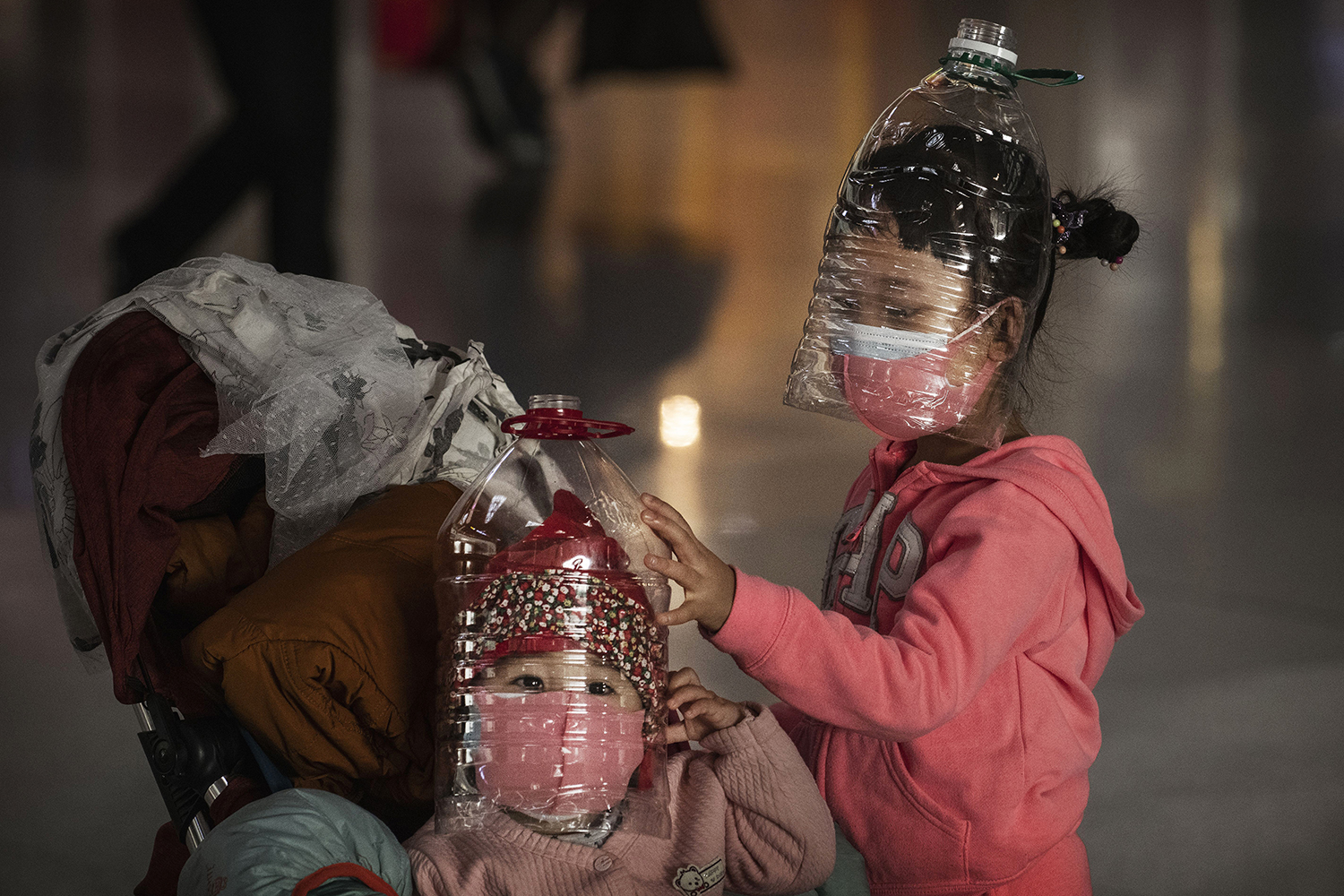 Children wear plastic bottles as makeshift masks while waiting to check in for a flight at Beijing Capital Airport on Jan. 30. The number of coronavirus cases at this point was more than 7,000 in mainland China. Kevin Frayer/Getty Images
