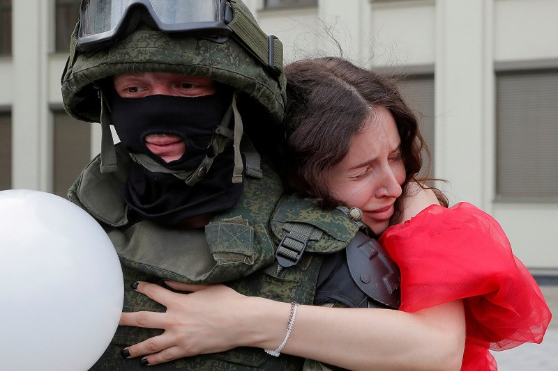 A protester embraces a member of the Belarusian Interior Ministry troops who was standing guard during a demonstration against police violence and rejecting the presidential election results in Minsk, Belarus, on Aug. 14. Vasily Fedosenko/REUTERS