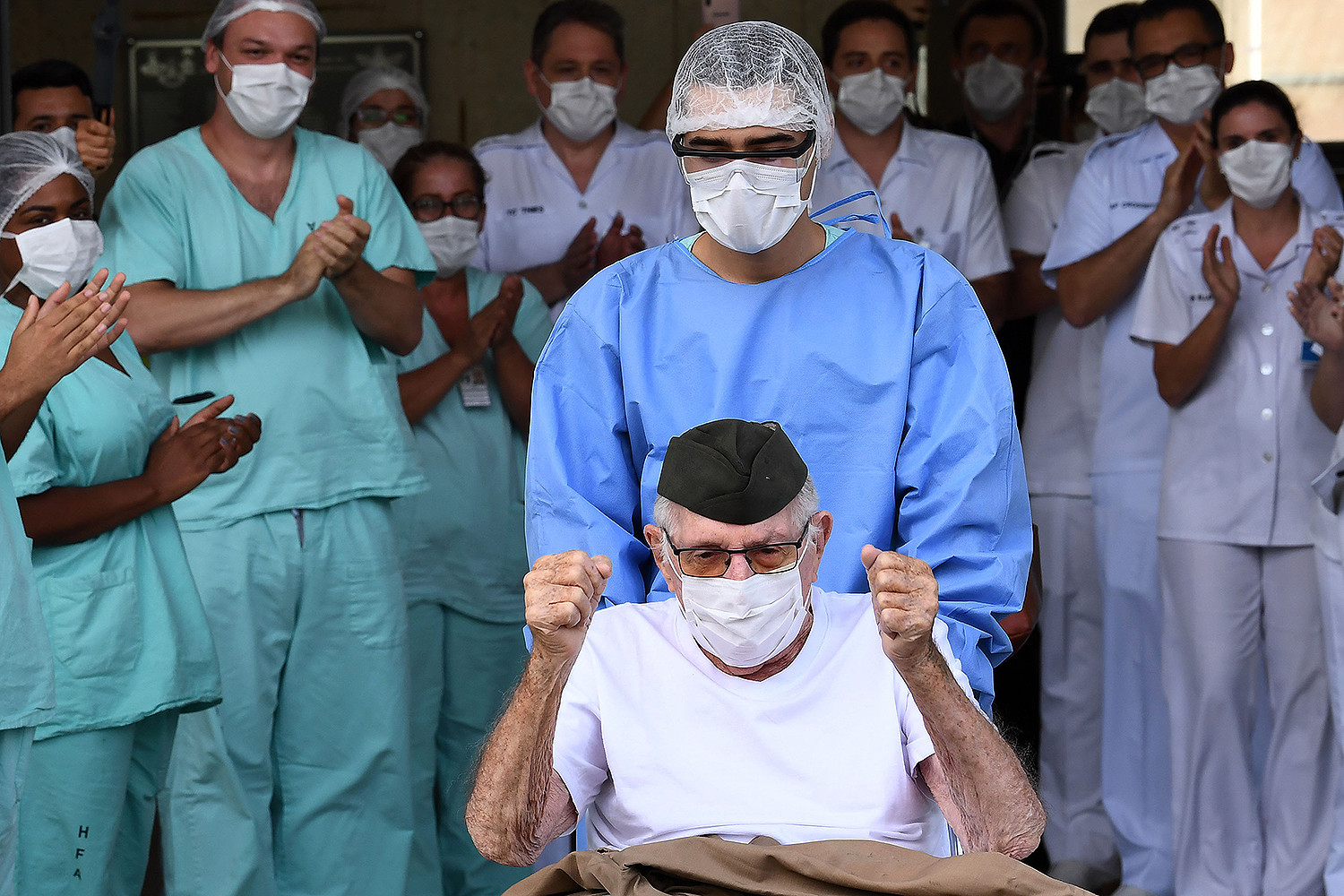 """Brazilian World War II veteran Ermando Armelino Piveta, 99, is discharged from the Armed Forces Hospital in Brasilia on April 14 after being treated for COVID-19. """"Winning this battle was for me bigger than winning the war,"""" he said. EVARISTO SA/AFP via Getty Images"""