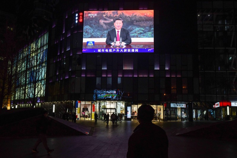 People walk below a giant screen showing news coverage of Chinese President Xi Jinping's speech
