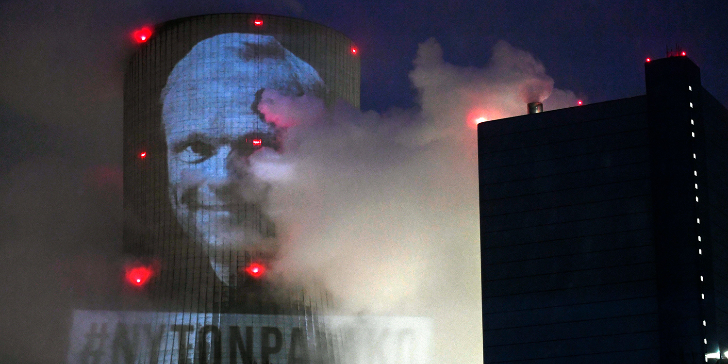 Greenpeace activists project an image of Pekka Lundmark, president and CEO of the Finnish utility company Fortum, onto the cooling tower of the coal-fired power plant Datteln 4 in Datteln, Germany, on Feb. 26. Climate activists occupied the controversial new coal power plant, preventing a test run of generators.