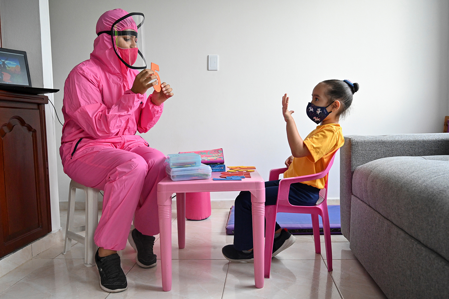 """A teacher wearing a biosecurity suit as a preventive measure against the spread of COVID-19 works with a girl at a home in Cali, Colombia, on Aug. 4 as part of a local kindergarten's """"teacher at home"""" program implemented to help children keep in touch with teachers and reduce the emotional impact of isolation. LUIS ROBAYO/AFP via Getty Images"""