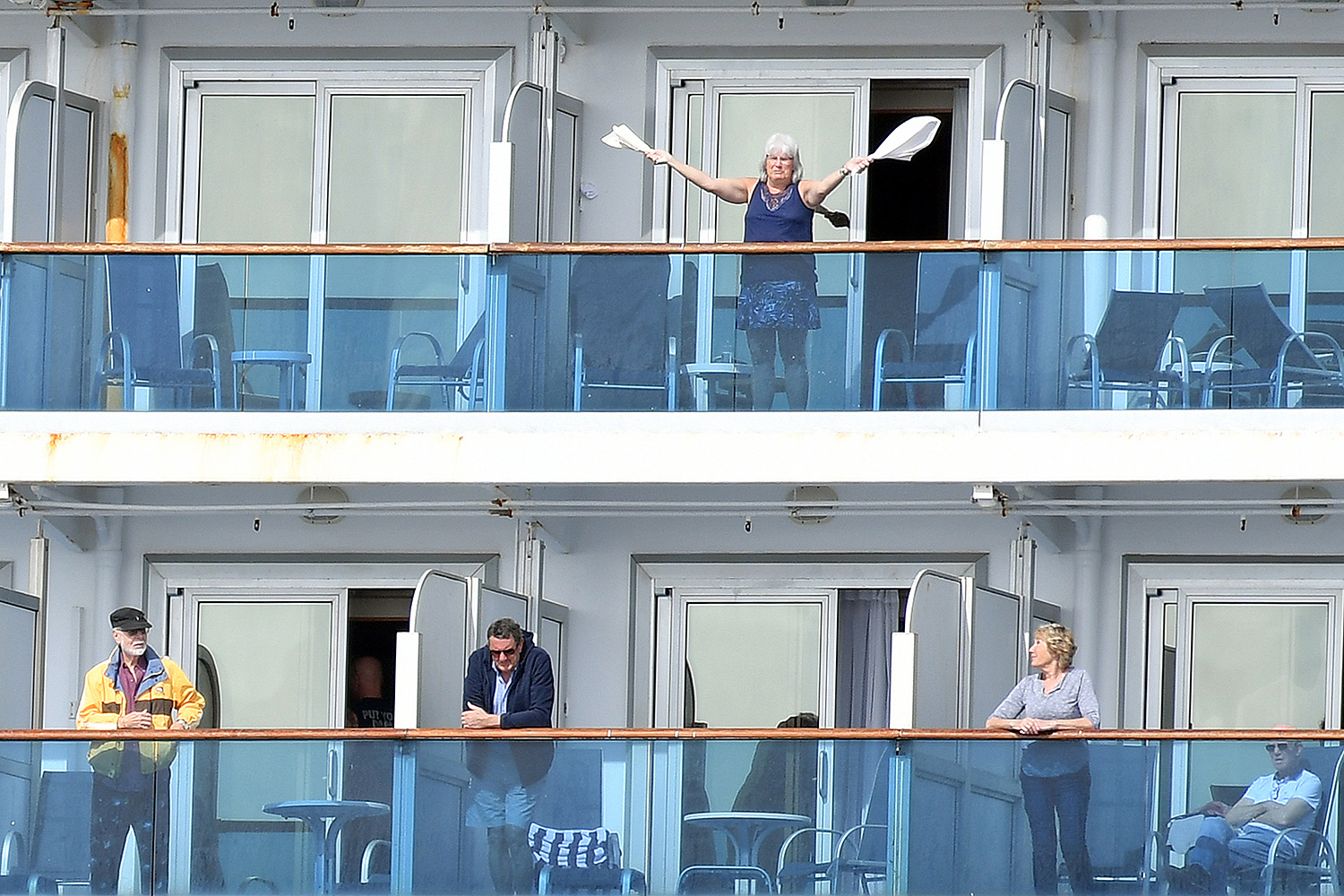 A woman gestures from aboard the coronavirus-stricken Grand Princess cruise ship as it maintains a holding pattern about 25 miles off the coast of San Francisco on March 8. On March 11, the World Health Organization declared the COVID-19 outbreak a pandemic. JOSH EDELSON/AFP via Getty Images