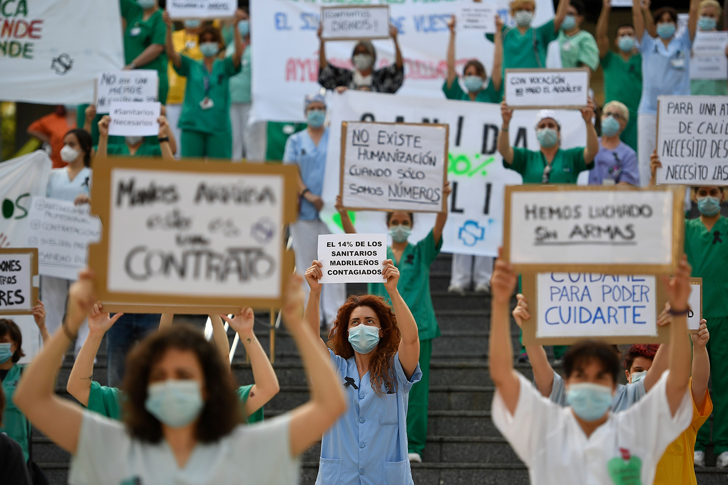 """Health care workers—including one (center) holding a sign that reads """"14% of healthcare workers in Madrid are infected""""—protest for a reinforced health care system outside the Gregorio Marañón Hospital in Madrid on May 25. PIERRE-PHILIPPE MARCOU/AFP via Getty Images"""