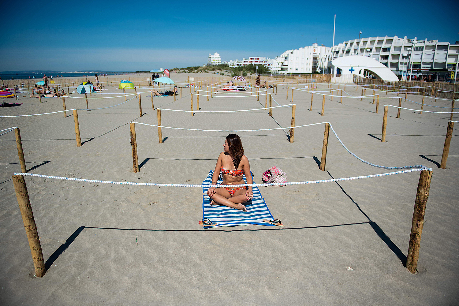 A woman sunbathes in a roped-off zone on the beach in La Grande Motte, southern France, on May 21, as the nation eased lockdown measures. CLEMENT MAHOUDEAU/AFP via Getty Images