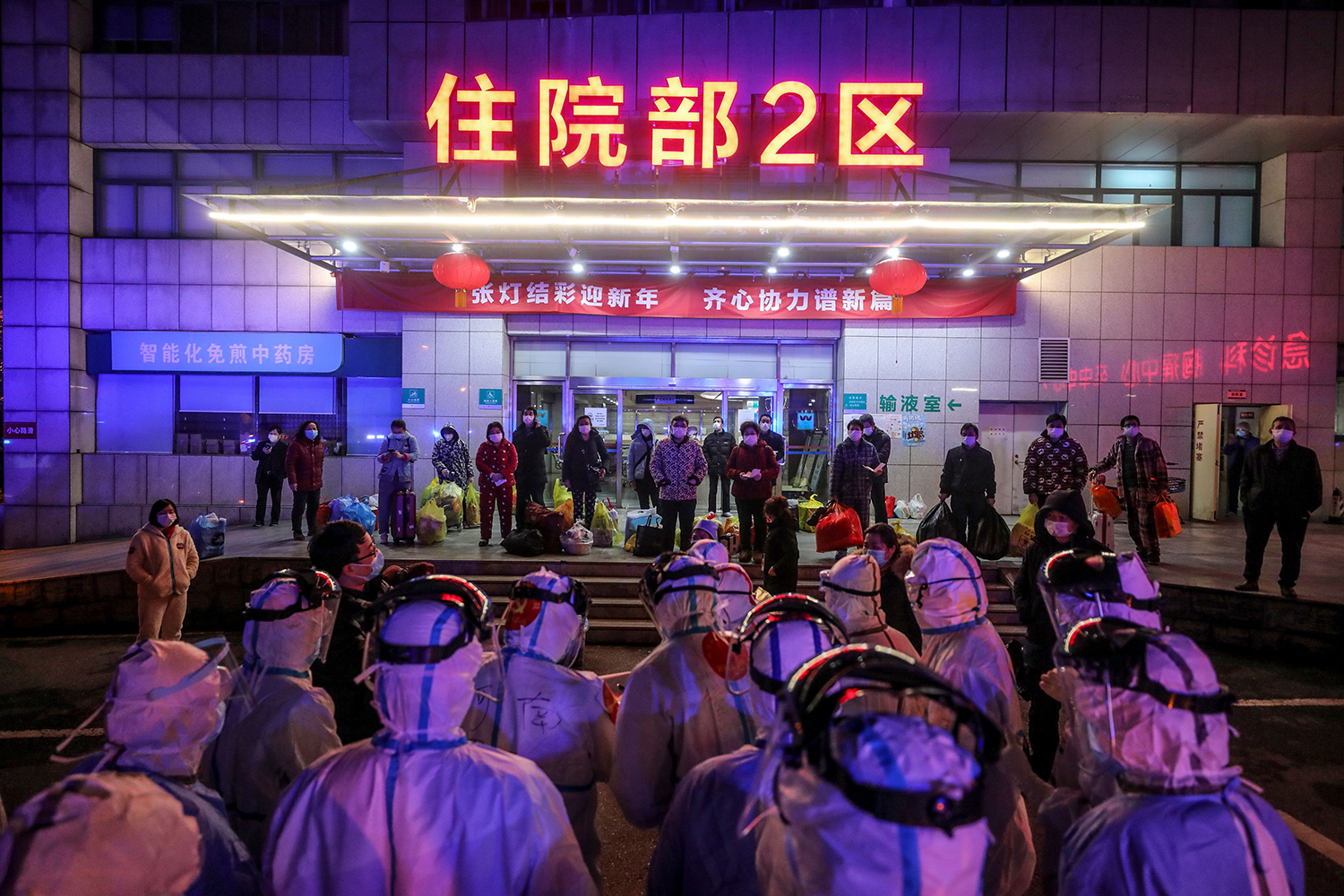 Coronavirus patients in Wuhan, China, line up at Wuhan No. 5 Hospital on March 3 as they wait to be transferred to Leishenshan Hospital, one of two new field hospitals built in under two weeks specifically for those infected by the virus. STR/AFP via Getty Images