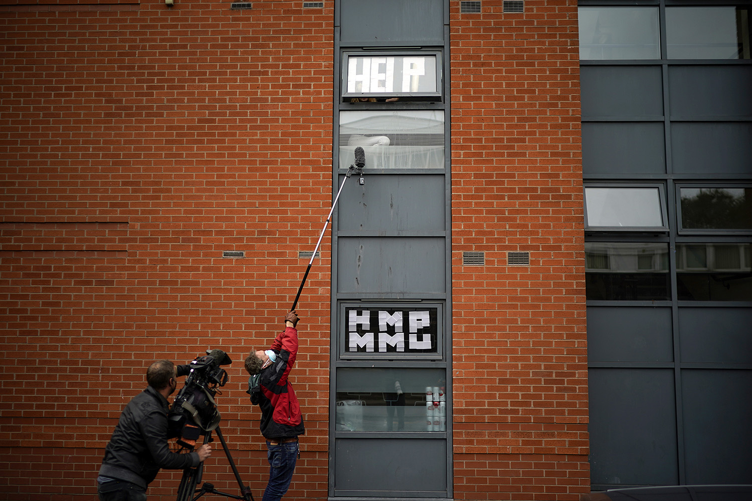 Isolating students peer out of their window as they are interviewed by a television crew in Manchester, England, on Sept. 28. Around 1,700 students across two student housing blocks were told to self-isolate for 14 days after more than 100 students tested positive for COVID-19. Christopher Furlong/Getty Images