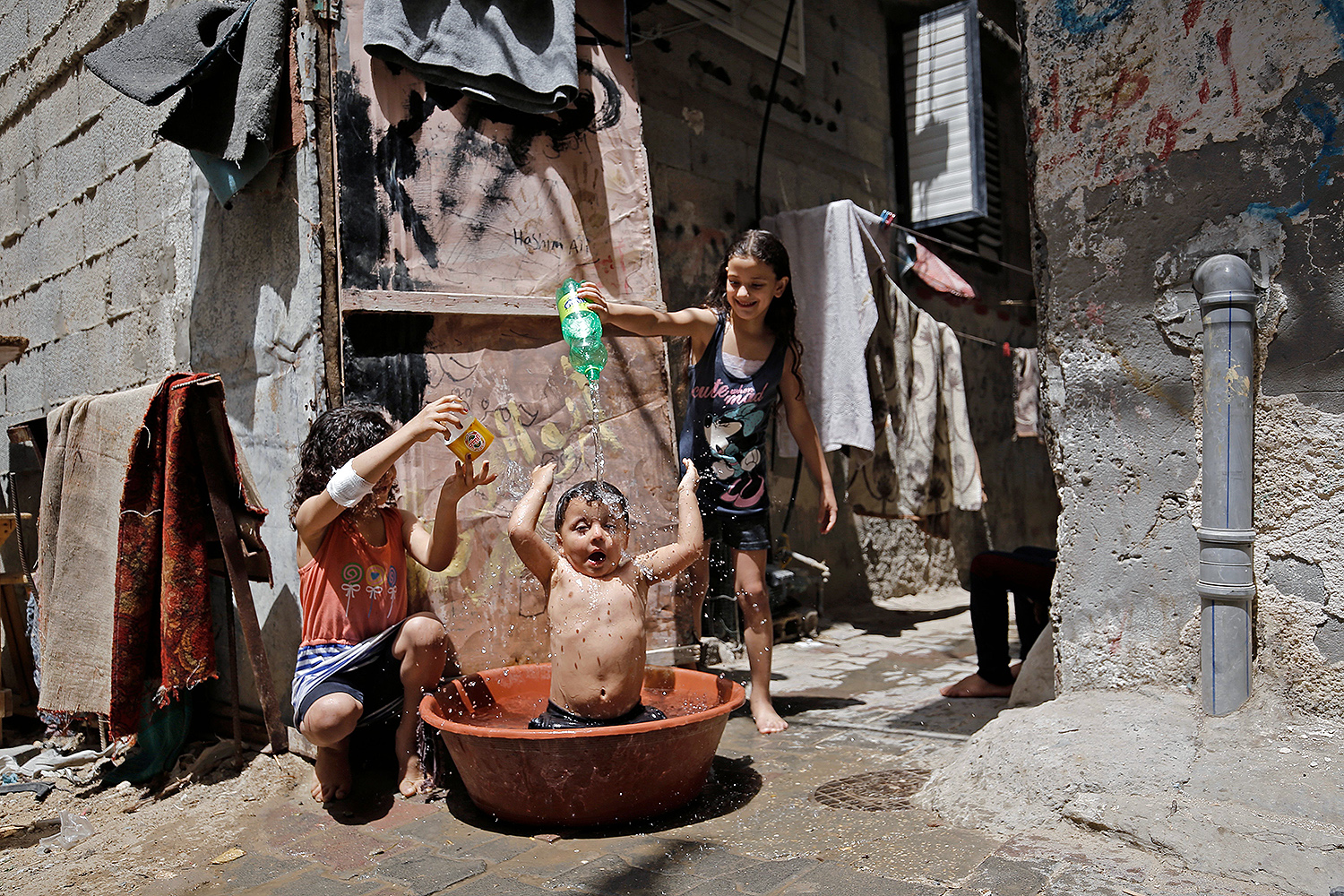 The simple things Palestinian girls pour water over a child's head to help him cool off during a heatwave at the Bureij refugee camp in the central Gaza Strip on May 19. MOHAMMED ABED/AFP via Getty Images