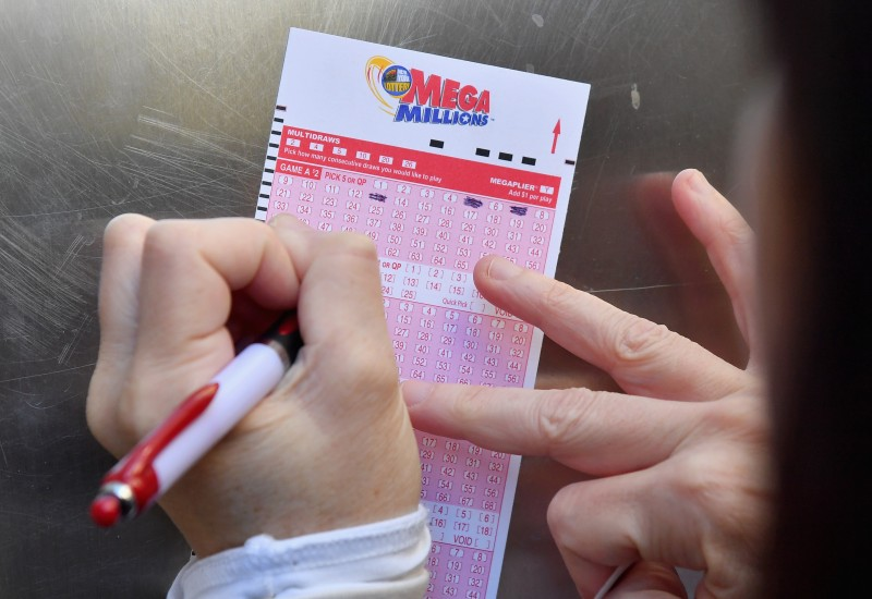 A woman fills out a Mega Millions lottery ticket on October 19, 2018 in New York City.
