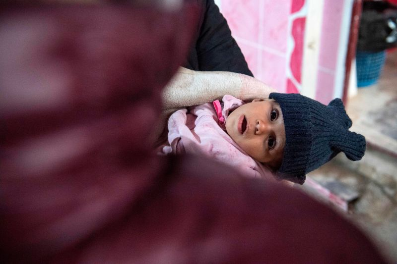 A woman carrying a child waits at a makeshift clinic at the Internally Displaced Persons (IDP) camp of al-Hol in al-Hasakeh governorate in northeastern Syria on February 7, 2019.