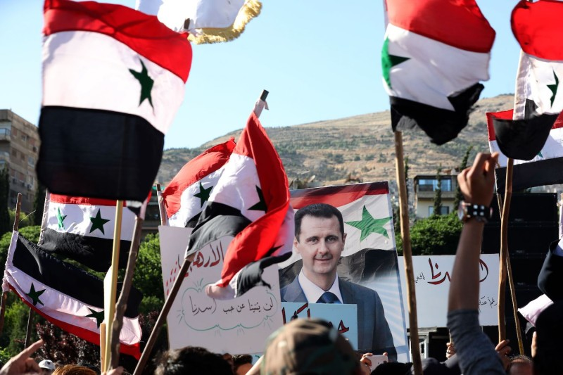 People wave Syrian national flags and pictures of President Bashar al-Assad