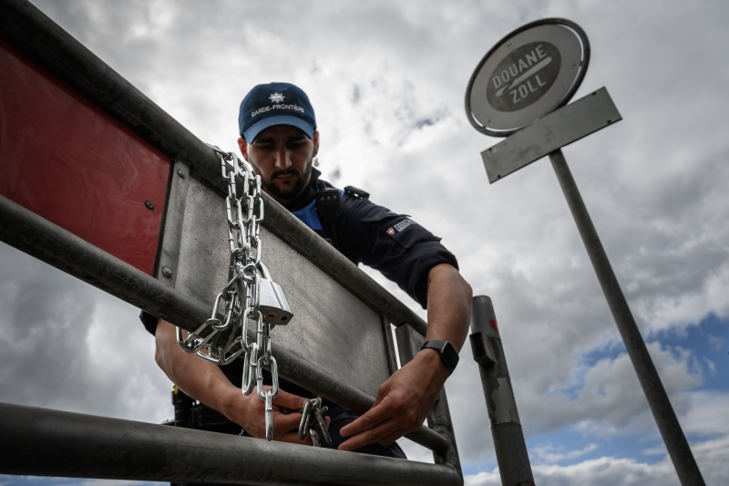 A Swiss customs officer attaches a chain to a fence after opening the Swiss-French border on June 14, 2020 in Thonex near Ambilly, France.