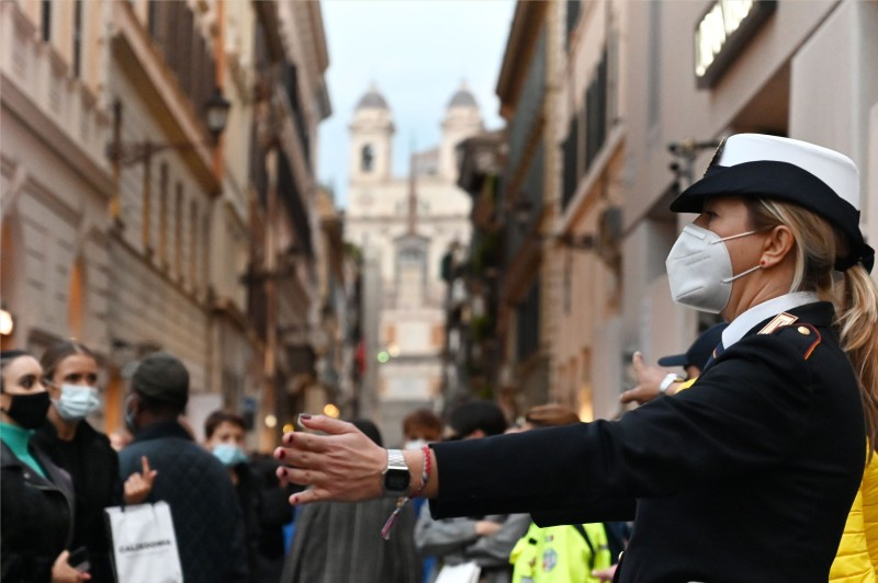 A municipal police officer wearing a face mask controls pedestrian traffic on Via dei Condotti in downtown Rome on Nov. 14. The Italian government imposed tighter restrictions on another five regions on Nov. 10.