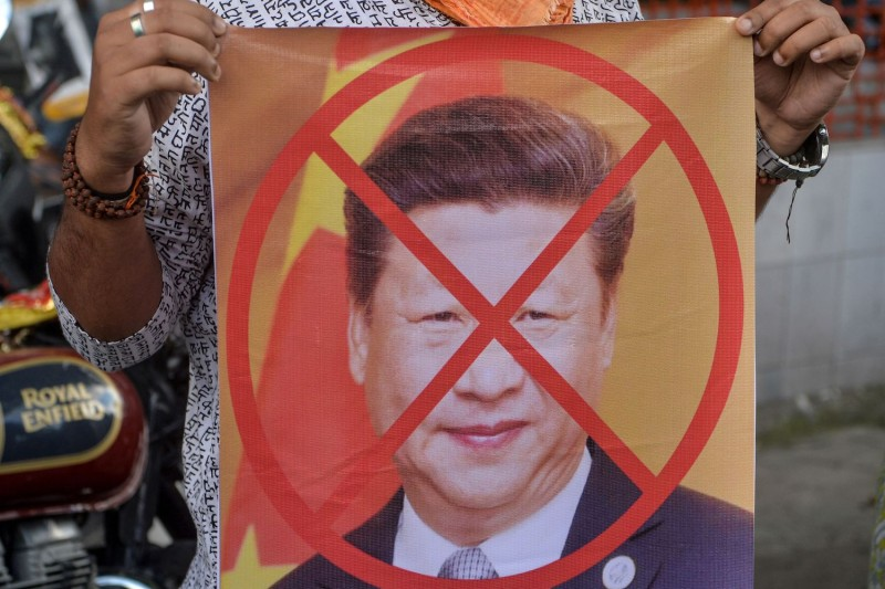 Bharatiya Janata Party activists hold a sign showing an X over the face of Chinese President Xi Jinping during an anti-China protest in Siliguri, India, on June 17.