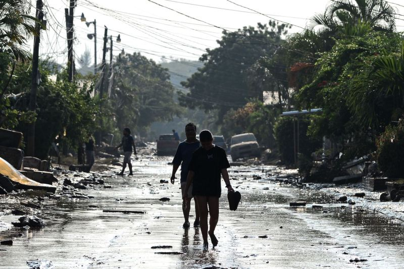 People walk along a street in Planeta, in the municipality of La Lima, Honduras after the passage of Hurricane Eta on Nov. 9.