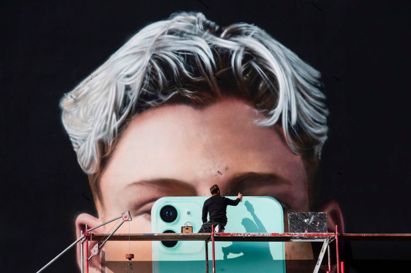 A graphic artist paints a mural ad for smartphone manufacturer Apple in Berlin on Oct 1.