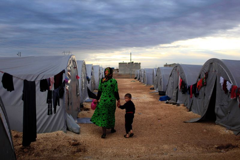 A Kurdish refugee mother and son from the Syrian town of Kobani walk beside their tent in a camp in the southeastern Turkish town of Suruc on the Turkish-Syrian border on Oct. 19, 2014.