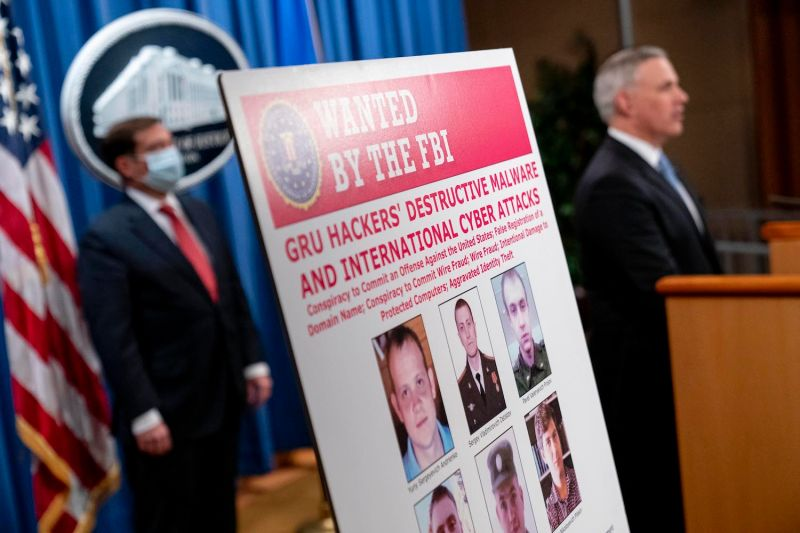A poster showing six wanted Russian military intelligence officers is displayed during news conference at the Department of Justice in Washington on Oct. 19.