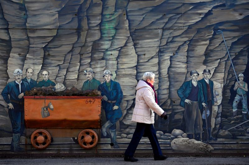 A woman walks past a mural of iron ore miners in Algrange, France, on Feb. 14, 2017.