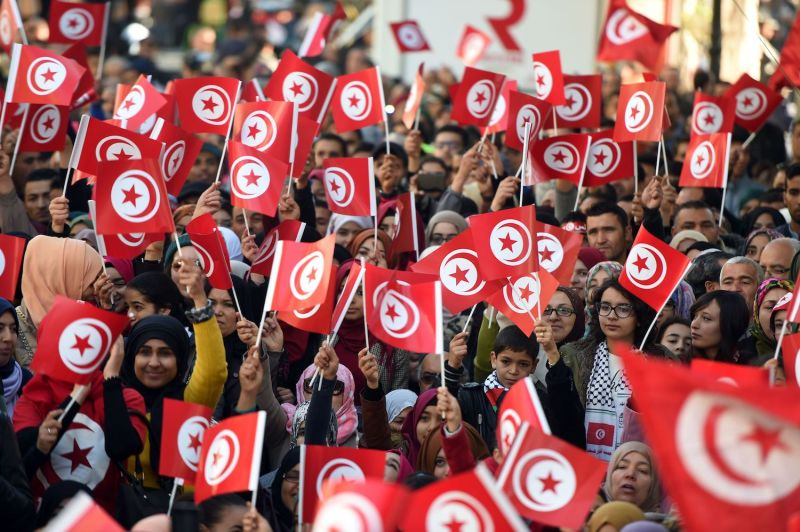 Tunisians wave national flags to mark the fifth anniversary of the 2011 revolution on Jan. 14, 2016.