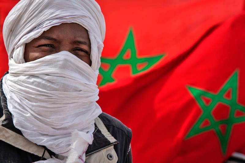 A tribesman stands in front of a Moroccan flag near the border in Western Sahara near Mauritania on Nov. 26.
