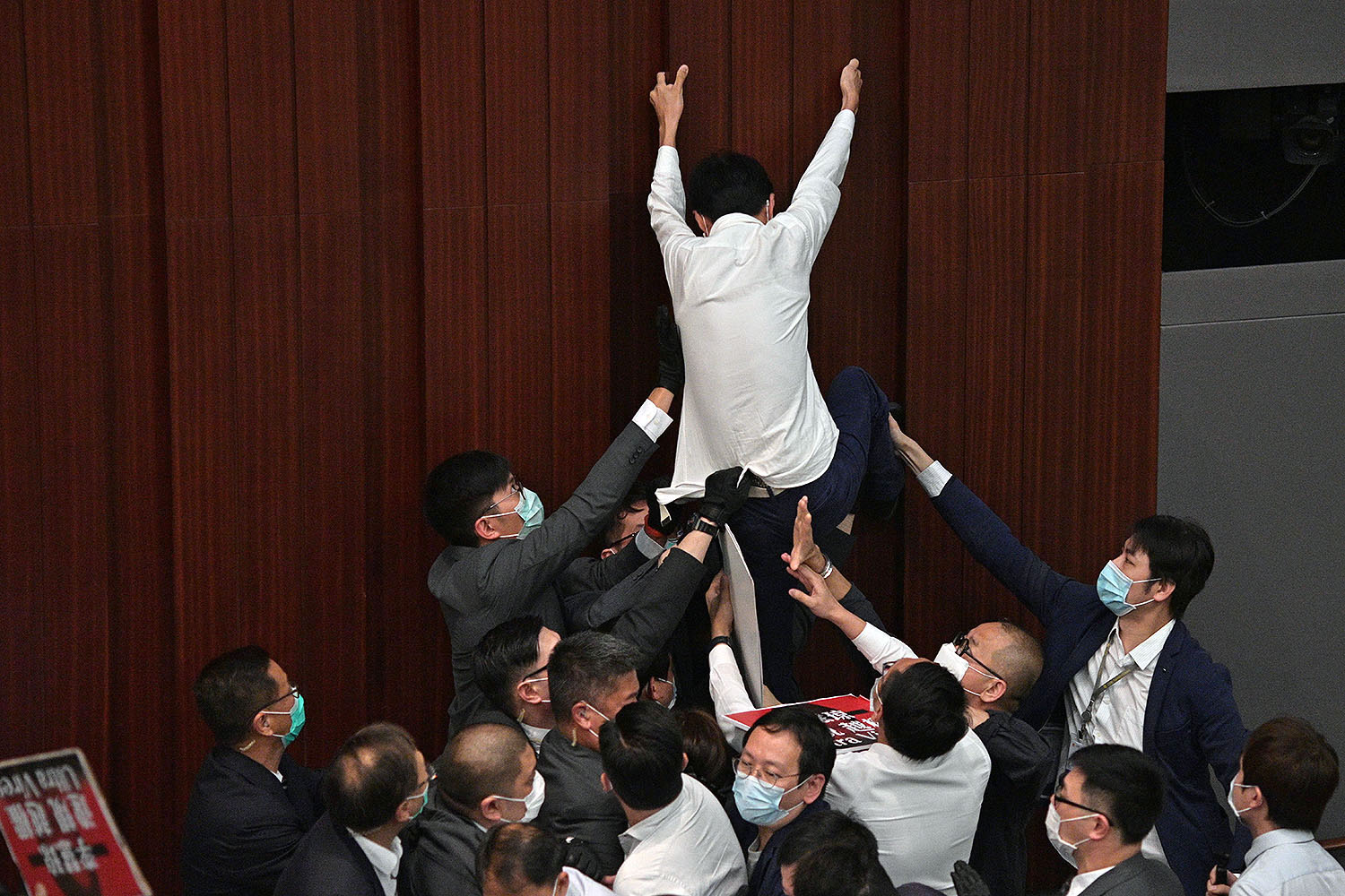 Pro-democracy lawmaker Eddie Chu Hoi-dick attempts to climb a wall as security members try to restrain him from protesting after pro-Beijing lawmaker Starry Lee (not seen) inserted herself as chair of a committee meeting at the Legislative Council in Hong Kong on May 8. ANTHONY WALLACE/AFP via Getty Images