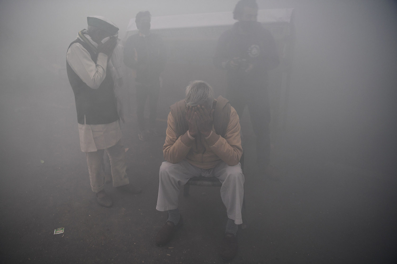 Farmers cover their faces amid fumigation by the municipal corporation near a roadblock at the Delhi-Uttar Pradesh state border in Ghazipur stopping farmers from marching to New Delhi to protest against the central government's recent agricultural reforms Dec. 1. SAJJAD HUSSAIN/AFP via Getty Images