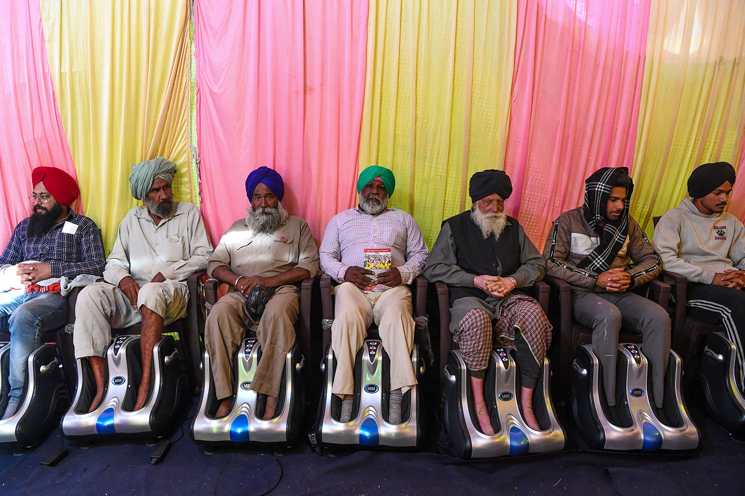 Indian farmers get foot massages inside a tent as they continue to demonstrate against the central government's recent agricultural reforms by blocking a highway at the Delhi-Haryana state border in Singhu on Dec. 21. SAJJAD HUSSAIN/AFP via Getty Images