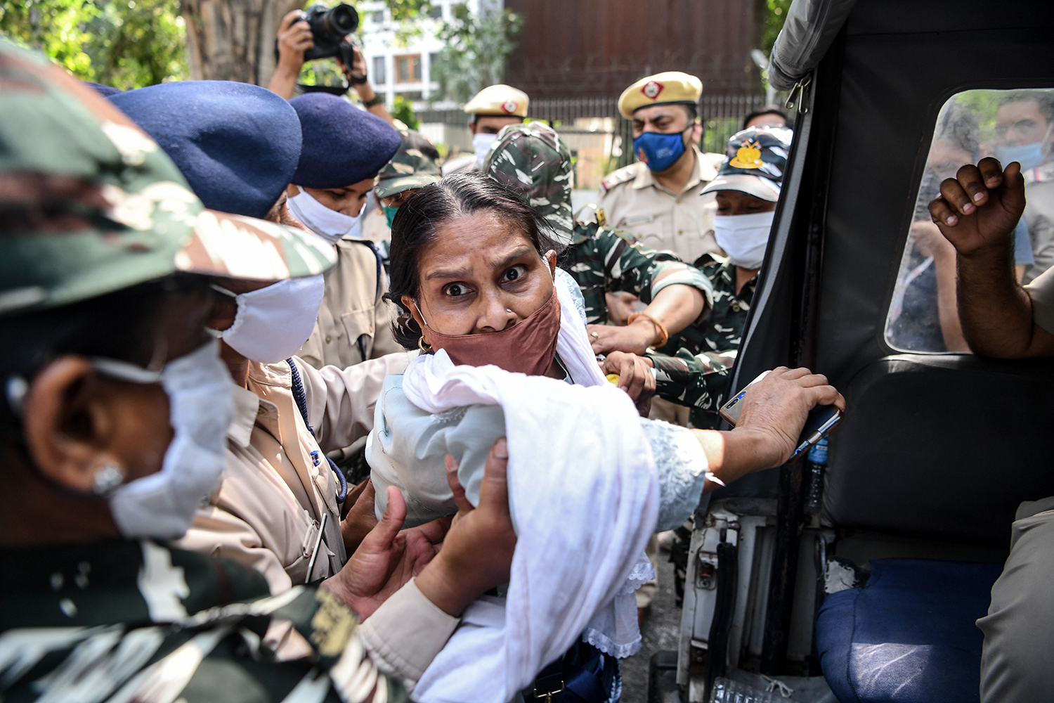 Security personnel detain a protester during a demonstration outside the Uttar Pradesh Bhawan in New Delhi on Sept. 30, a day after a 19-year-old woman who was allegedly gang-raped died from her injuries. Indian police were accused of forcibly cremating the victim's body. SAJJAD HUSSAIN/AFP via Getty Images