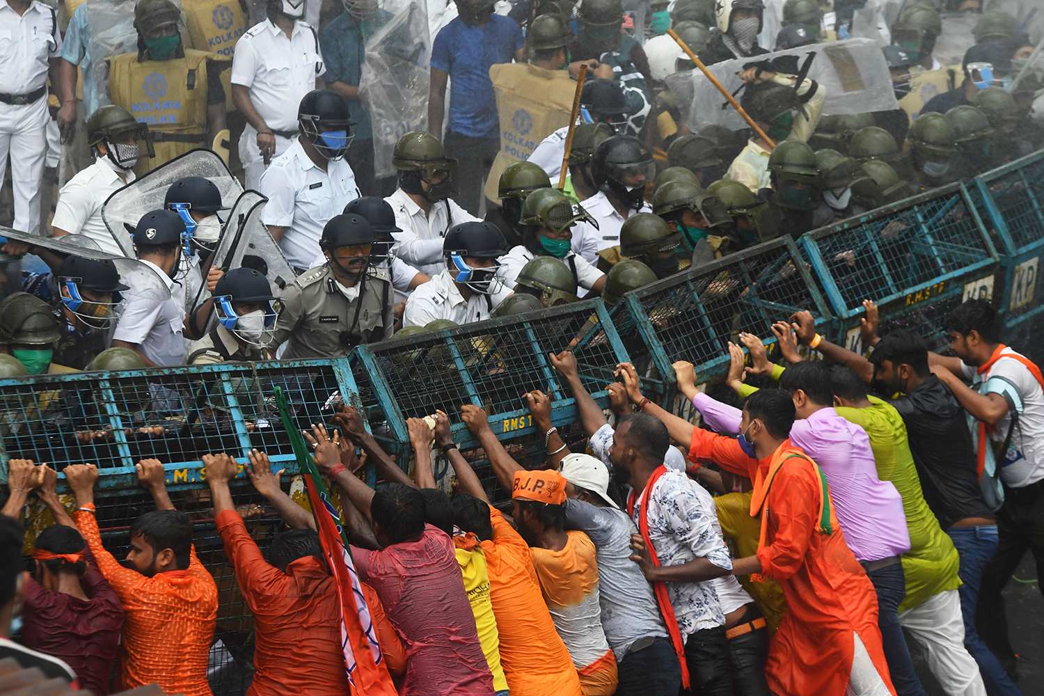 "Activists of the Bharatiya Janata Party try to break through a police barricade during a protest march toward the office of West Bengal Chief Minister Mamata Banerjee in  Kolkata, India, on Oct. 8 to protest against the ""worsening"" law and order situation in the state. DIBYANGSHU SARKAR/AFP via Getty Images"