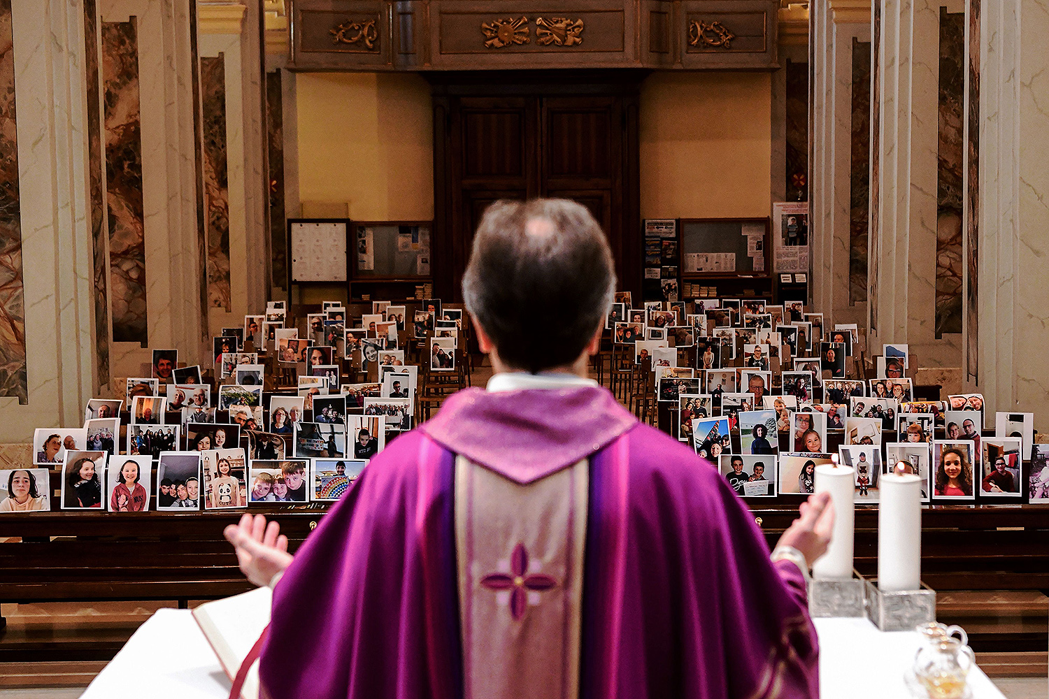 The Rev. Giuseppe Corbari, a priest in the village of Robbiano, Italy, near Milan, celebrates Mass in front of photographs of his congregation attached to empty pews March 22. The priest appealed to his parishioners to send him selfies so he wouldn't be alone when celebrating Mass. PIERO CRUCIATTI/AFP via Getty Images