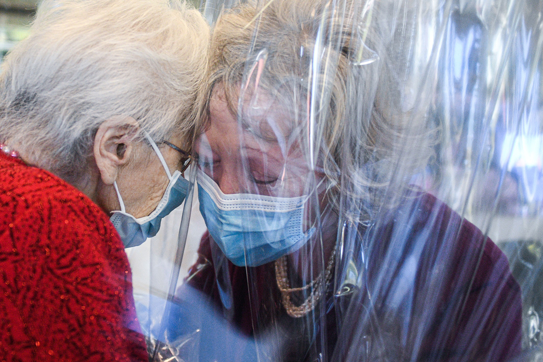"A resident (left) of the Domenico Sartor nursing home in Castelfranco Veneto, near Venice, Italy, hugs her visiting daughter through a plastic barrier in a ""Hug Room"" on Nov. 11. PIERO CRUCIATTI/AFP via Getty Images"