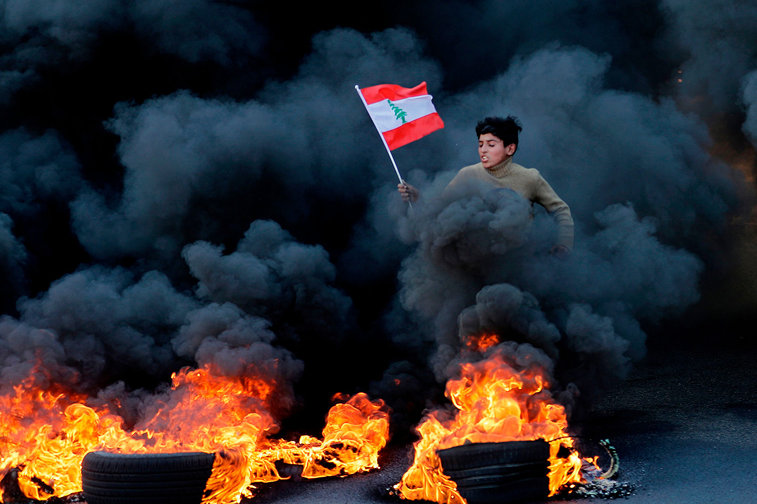 A Lebanese youth runs with a national flag as smoke billows from burning tires during a demonstration in Jal el-Dib area on the northern outskirts of Beirut on Jan. 14. JOSEPH EID/AFP via Getty Images