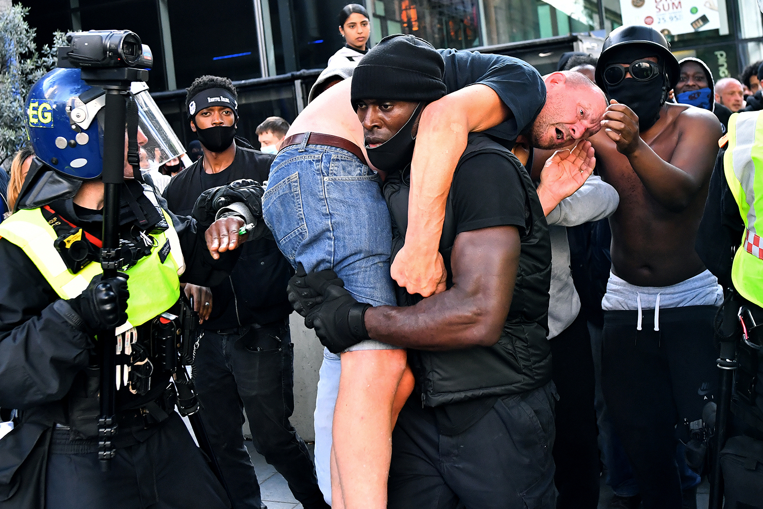 Patrick Hutchinson, a demonstrator participating in a Black Lives Matter protest in London, carries a suspected far-right counterprotester who was injured to safety near Waterloo station June 13. Dylan Martinez/REUTERS