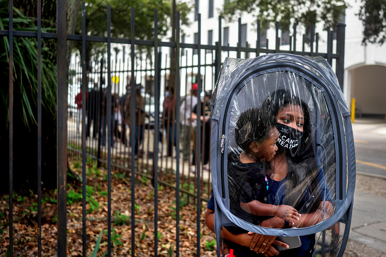 Dana Clark and her 18-month-old son, Mason, wait in line at City Hall in New Orleans on Oct. 16 as early voting begins for the upcoming presidential election. Clark said she donned the protective plastic cover because didn't know how many people would be wearing masks in line, and her child doesn't have one. She also works as a teacher and wanted to take precautions for her students' sakes. Kathleen Flynn/REUTERS