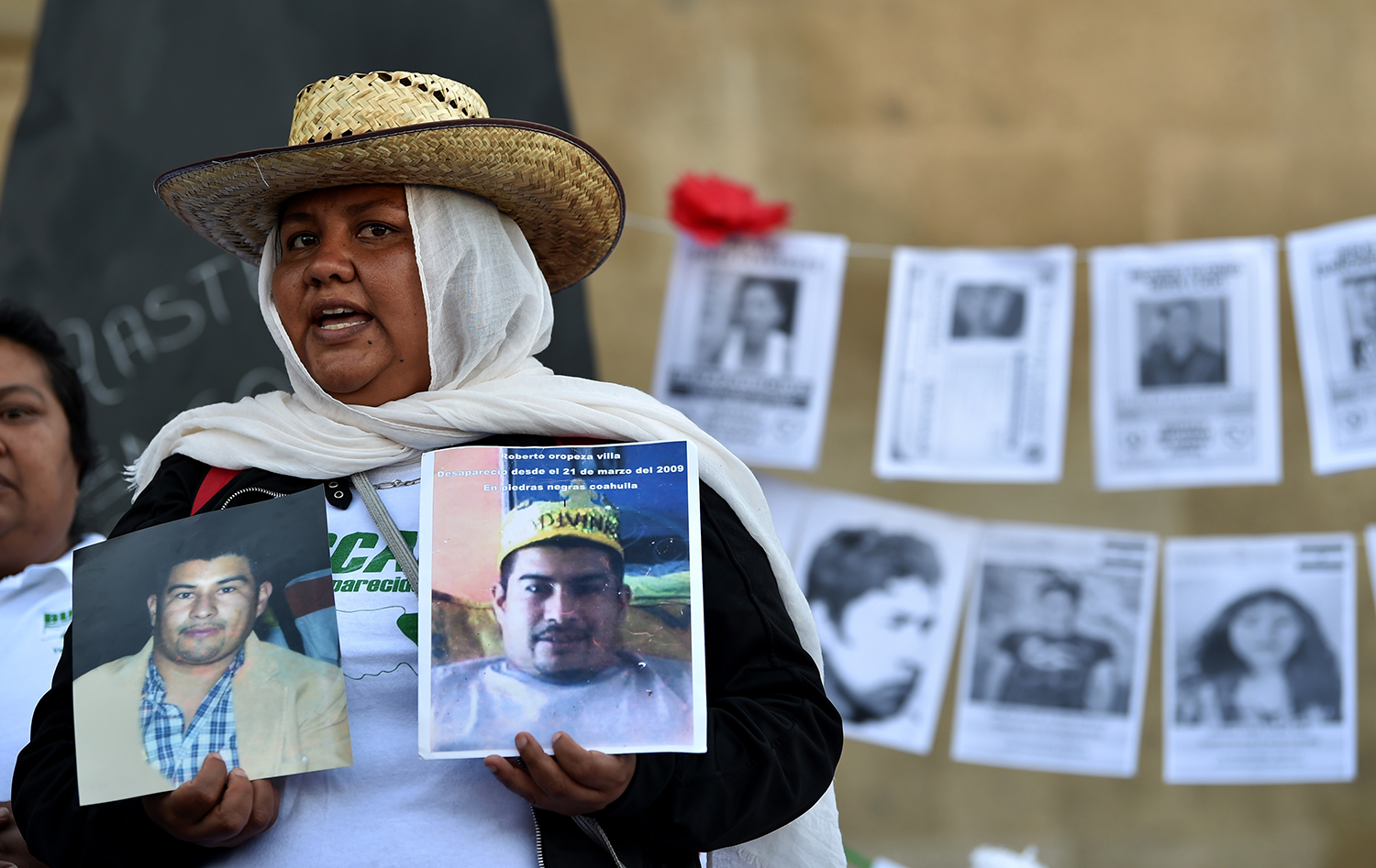 A woman holds pictures of a missing relative in front of the National Palace during the commemoration of the International Day of the Disappeared in Mexico City on Aug. 30, 2019. Tens of thousands of people are missing in Mexico amid years of violence since the government declared war on the country's powerful drug cartels.