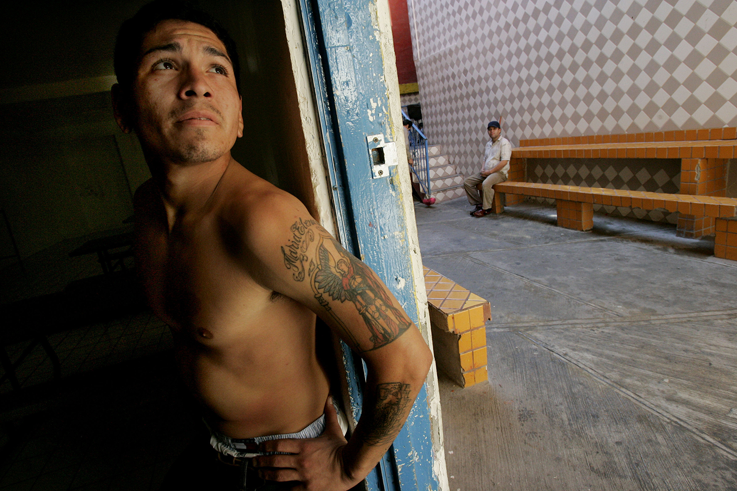 A recovering heroin addict stands in a doorway after exercising at the Los Tesoros Escondidos Drug Rehabilitation Center in Tijuana, Mexico, on Dec. 14, 2006.