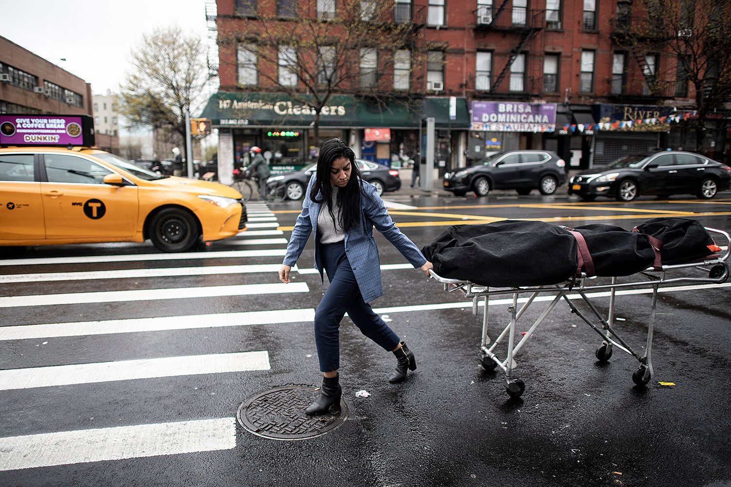 Alisha Narvaez, a manager at International Funeral & Cremation Services, transports a body to the funeral home in the Harlem neighborhood of New York City on April 24. JOHANNES EISELE/AFP via Getty Images