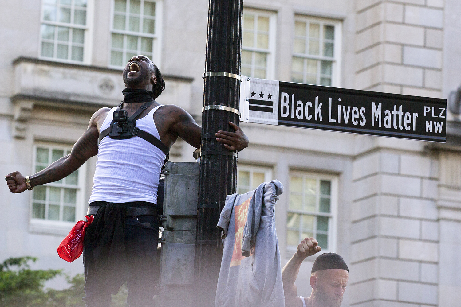 Mike D'angelo screams while holding on to a street sign newly named Black Lives Matter Plaza during a demonstration against racism and police brutality near the White House in Washington, D.C., on June 6. JOSE LUIS MAGANA/AFP via Getty Images