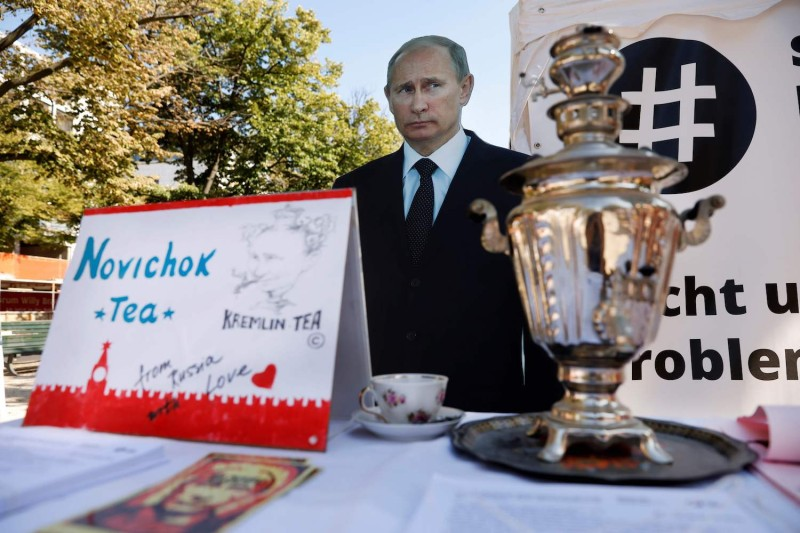 "A mock offer of ""Novichok Tea"" is seen in front of an image of Russian President Vladimir Putin outside the Russian embassy in Berlin during a protest on September 23, 2020. (Odd Anderson/AFP/ Getty Images)"