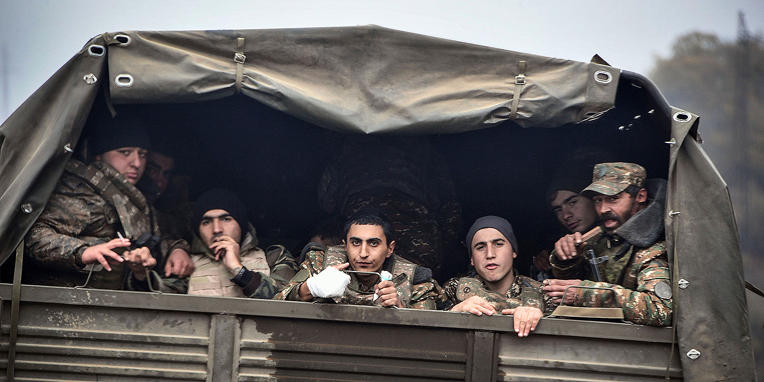 Armenian soldiers look out from their truck outside the disputed province's capital of Stepanakert on Nov. 12 during the military conflict between Armenia and Azerbaijan over the breakaway region of Nagorno-Karabakh. The fighting that broke out Sept. 27 has been the heaviest since a 1994 ceasefire and has threatened to draw in regional powers Turkey, which backs Azerbaijan, and Russia, which has a military alliance with Armenia.
