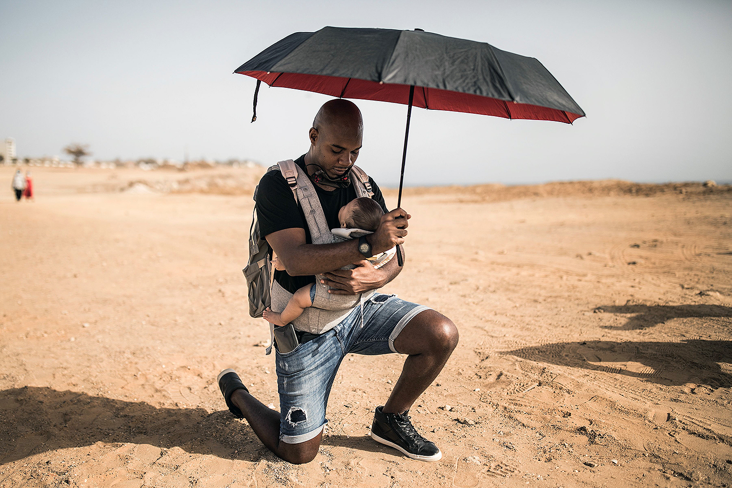 A man named Alexis kneels with his baby at a protest in solidarity with the Black Lives Matter movement in Dakar, Senegal, on June 9. JOHN WESSELS/AFP via Getty Images