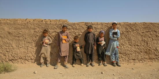 Young boys return home to the Shahrak-e-Sabz camp after finishing their classes at school on Oct. 7.