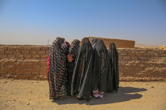 Women at the Shahrak-e-Sabz camp wait for a ride to take them to the Kahdistan health clinic in Herat on Oct. 7.