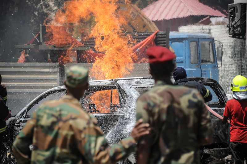 Members of the Somali military watch as firefighters work to extinguish a blaze after a car bomb exploded in Mogadishu on Jan. 29, 2019.