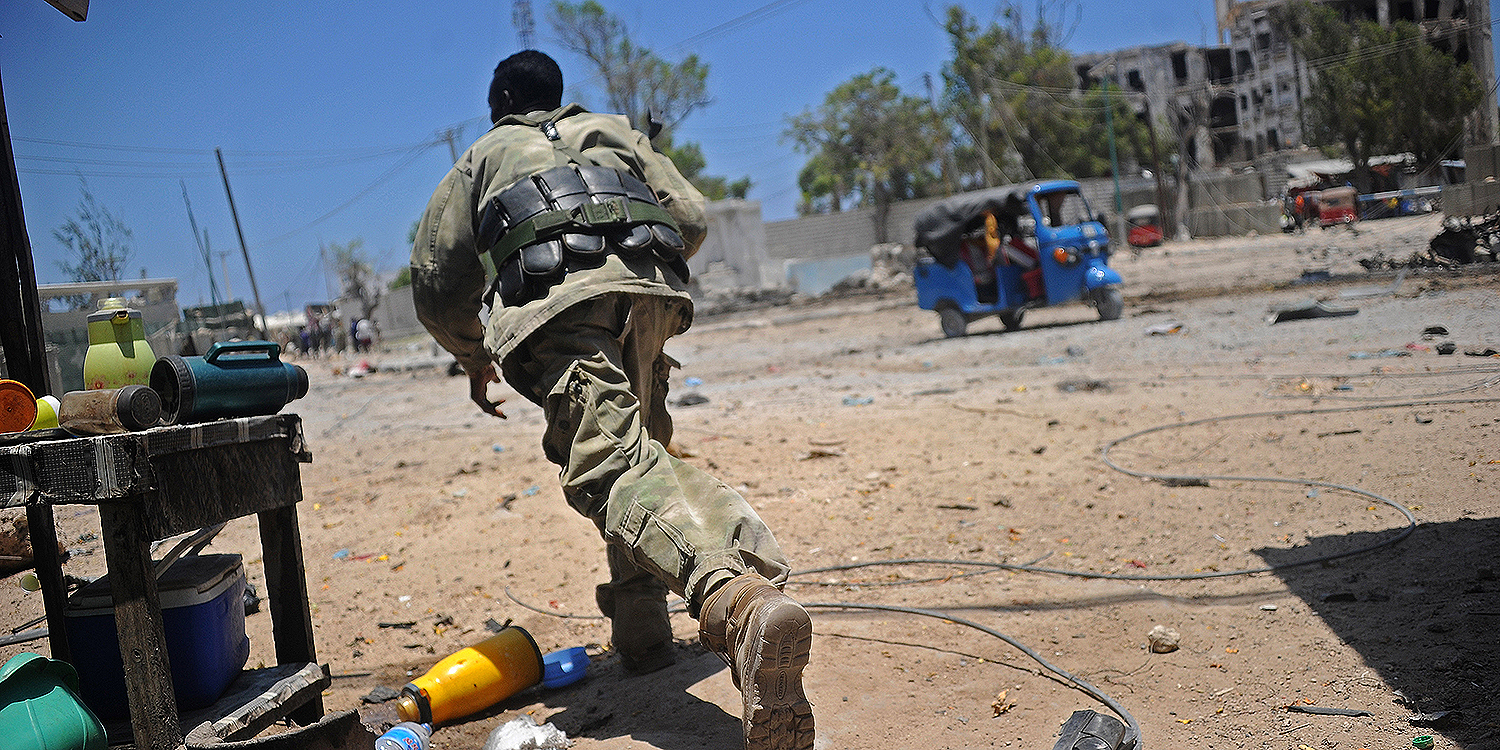 A Somali soldier runs for cover at the scene of two explosions set off near the ministries of public works and labor in Mogadishu on March 23, 2019. The Al-Shabaab jihadist group claimed responsibility.