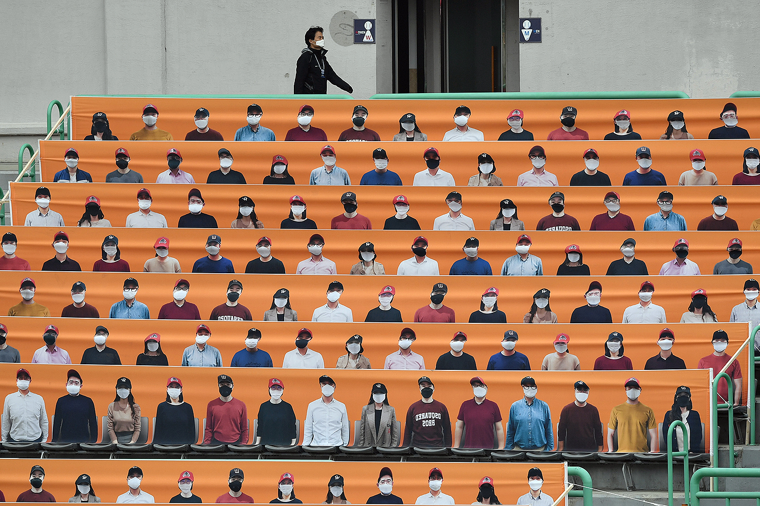A man walks past banners depicting spectators in the stands prior to South Korea's new baseball season opening game in Incheon on May 5. JUNG YEON-JE/AFP via Getty Images