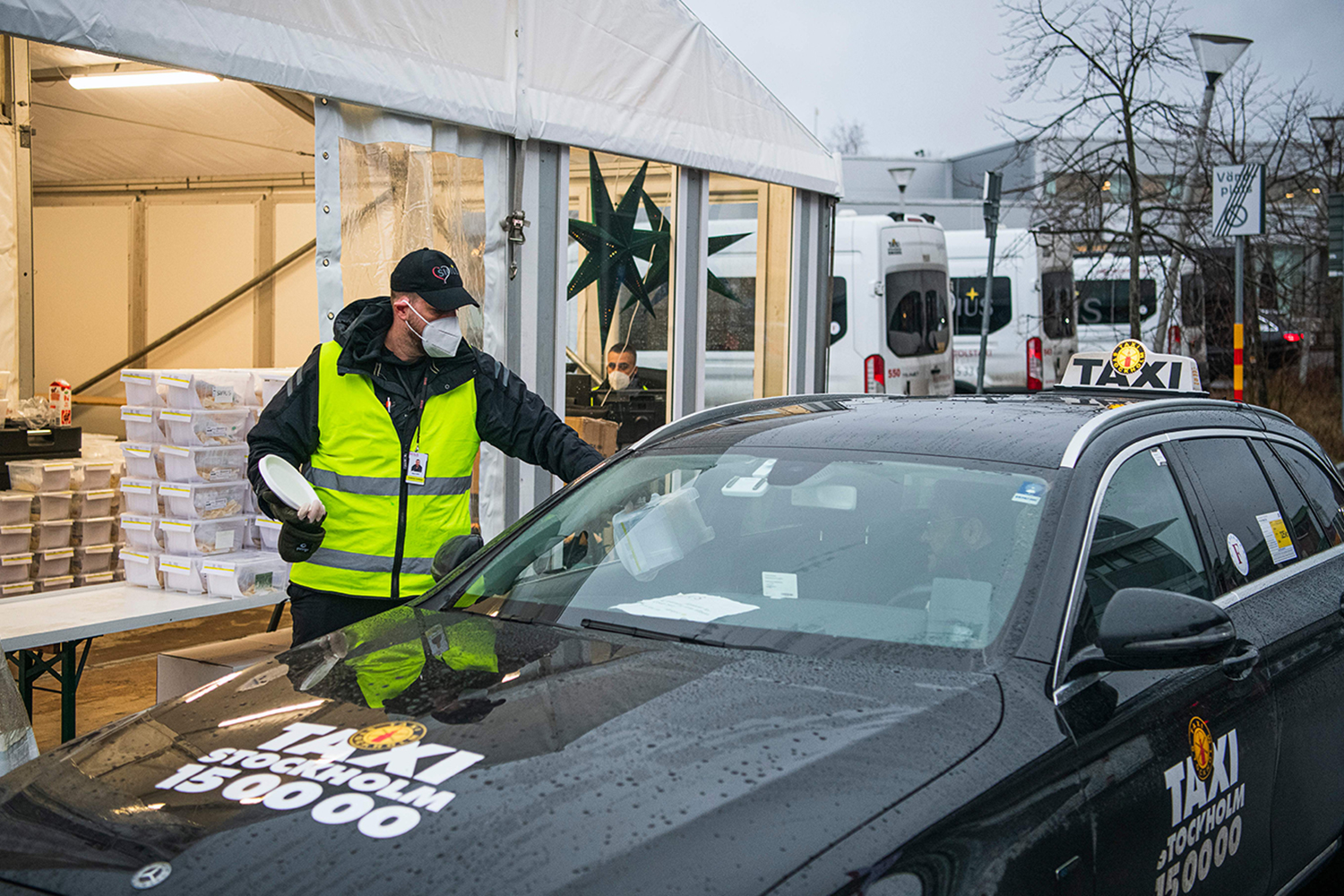 A Taxi Stockholm driver collects COVID-19 test kits from a station in Stockholm on Dec. 4. Drivers from two firms deliver around 25,000 tests a week in the region to people who suspect they have the coronavirus, according to Karolinska University Hospital, which is involved in testing in the area.